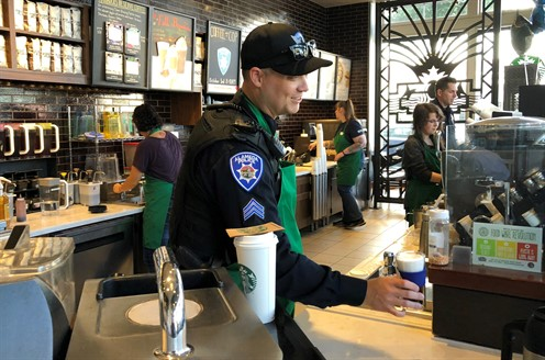 An Alameda Police sergeant serves coffee to patron during a Coffee with a Cop event.